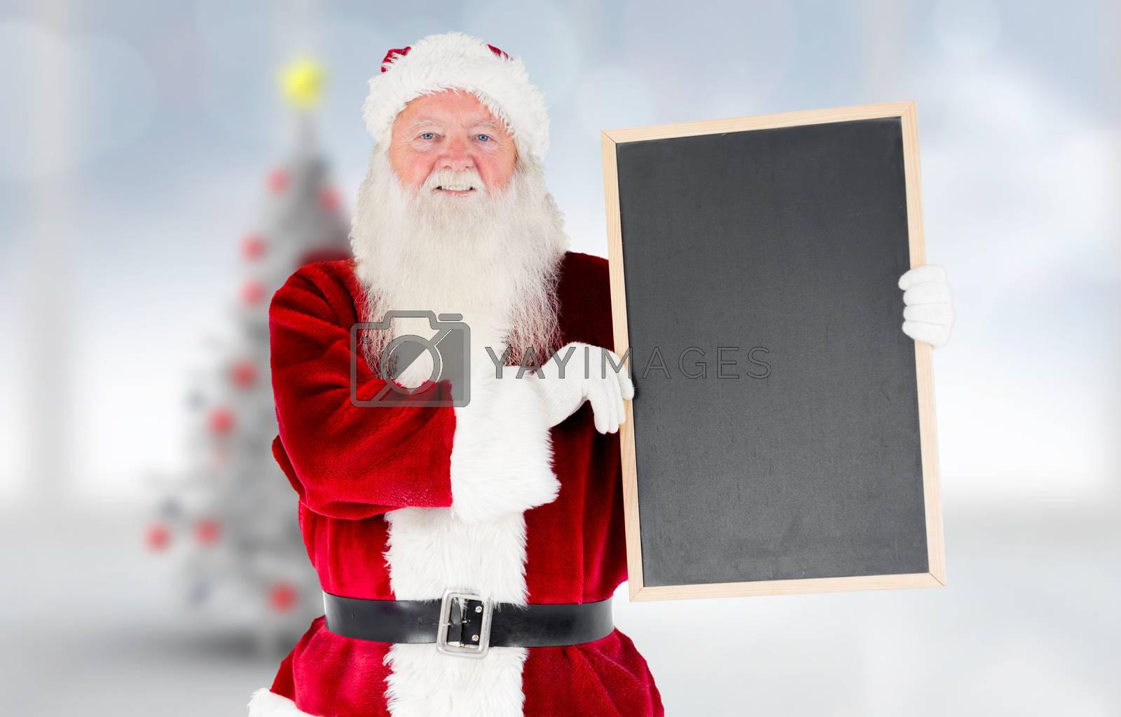 Santa claus showing blackboard against blurry christmas tree in room