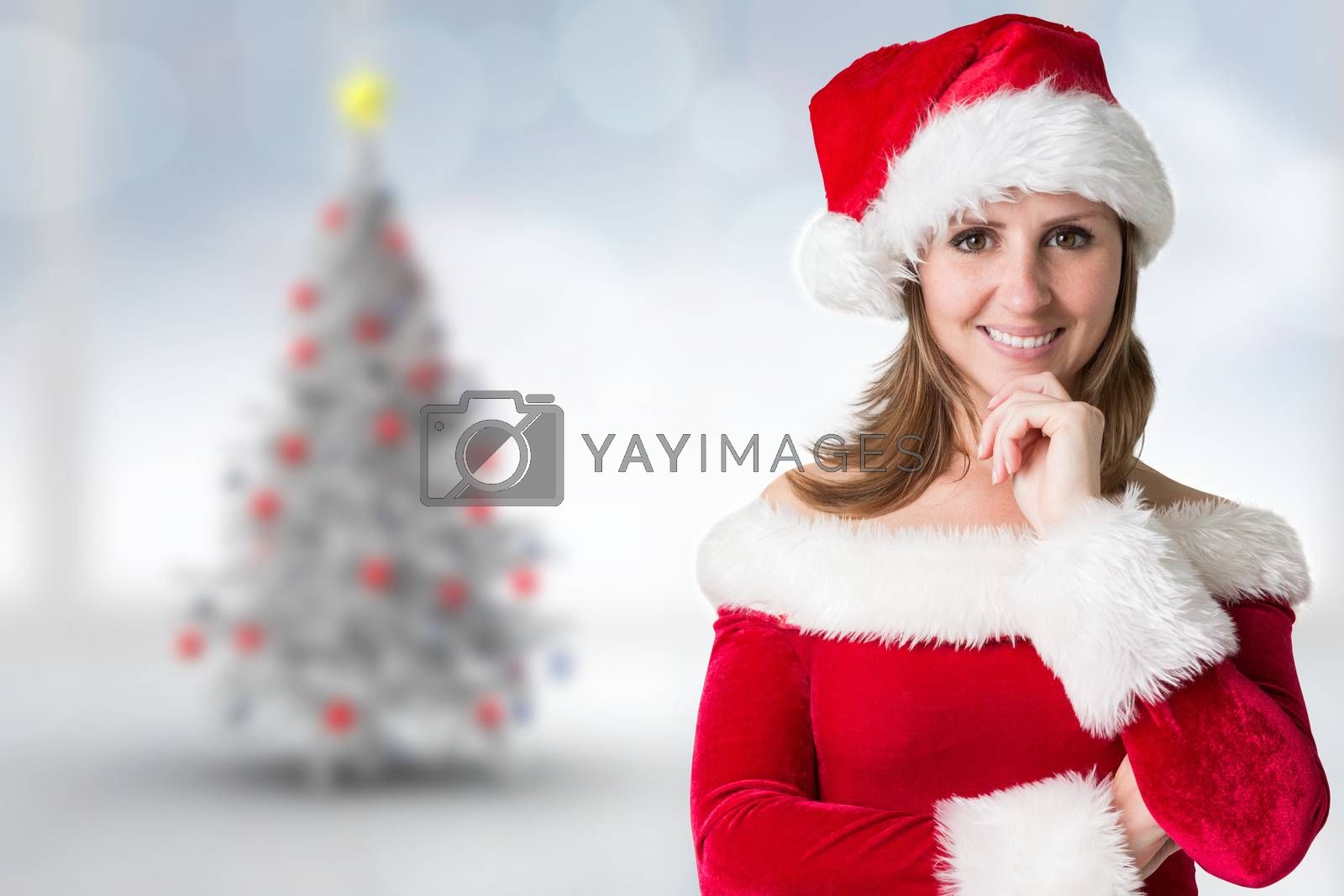 Pretty girl in santa outfit against blurry christmas tree in room