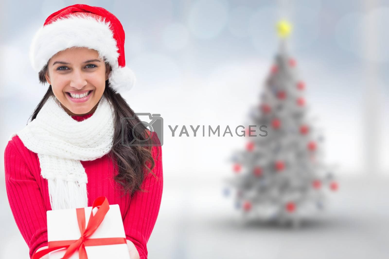 Festive brunette holding gift against blurry christmas tree in room