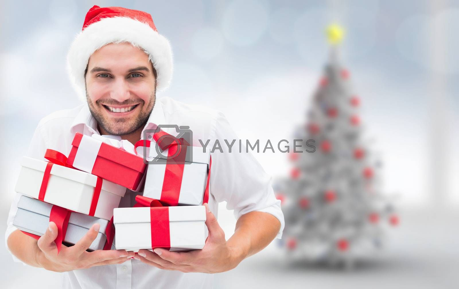 Festive man holding christmas gifts against blurry christmas tree in room