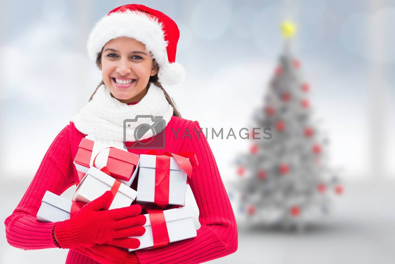 Festive brunette holding gifts against blurry christmas tree in room