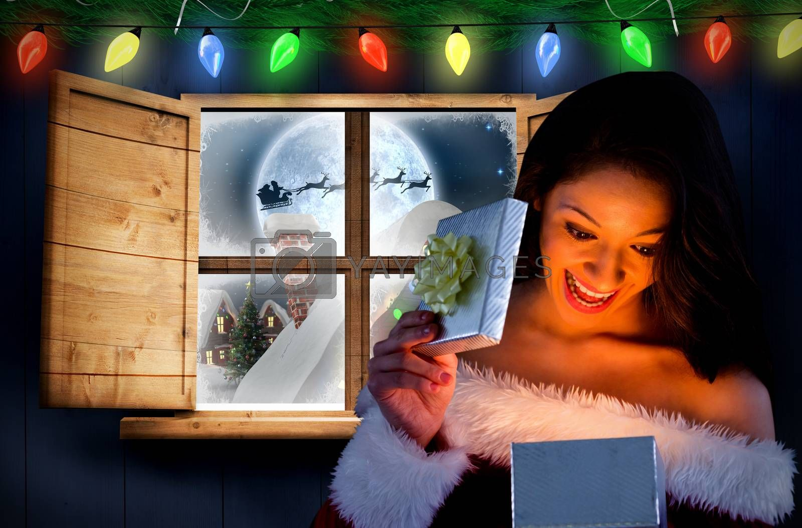 Sexy santa girl opening gift against santa delivery presents to village