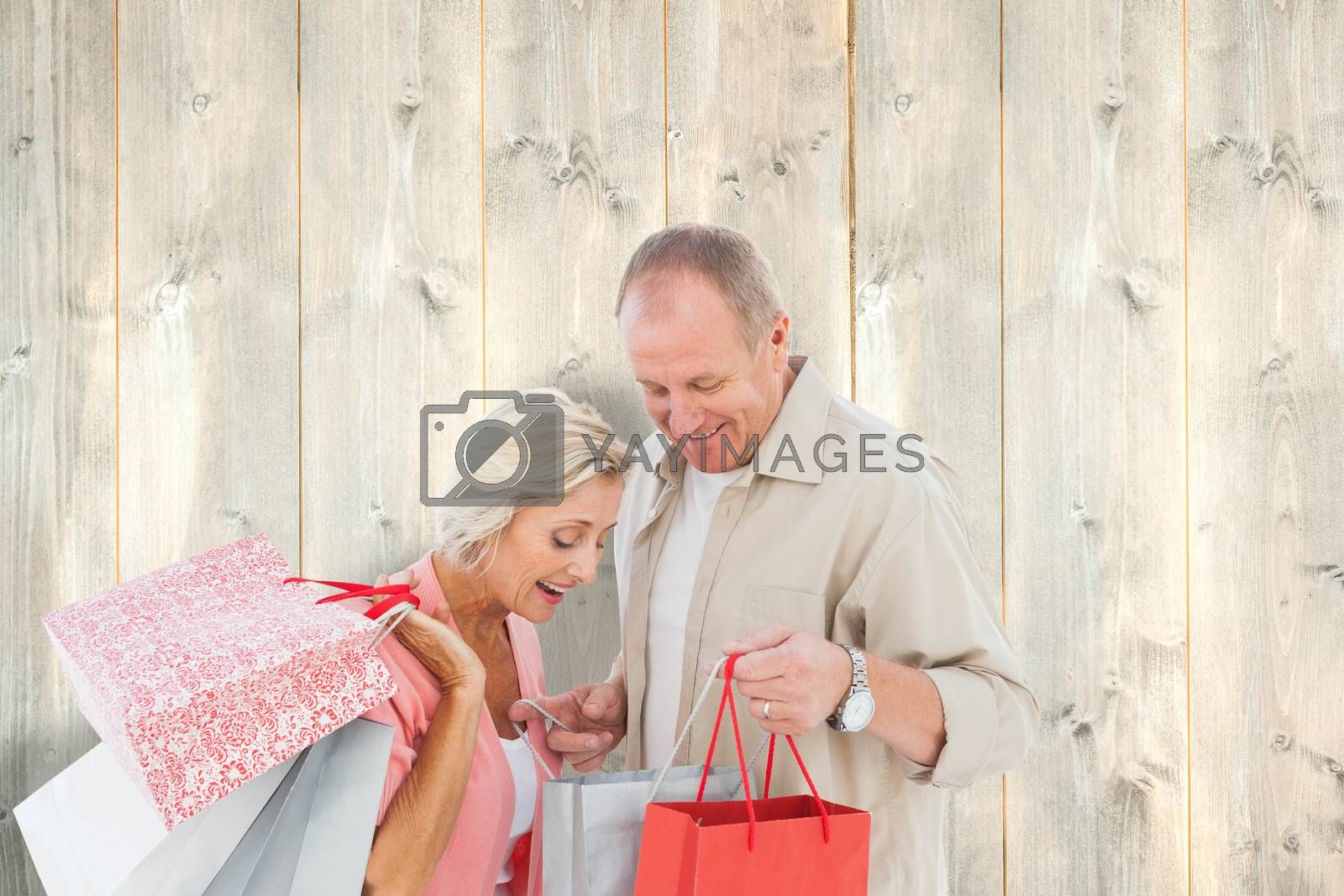 Couple with shopping bags against pale wooden planks