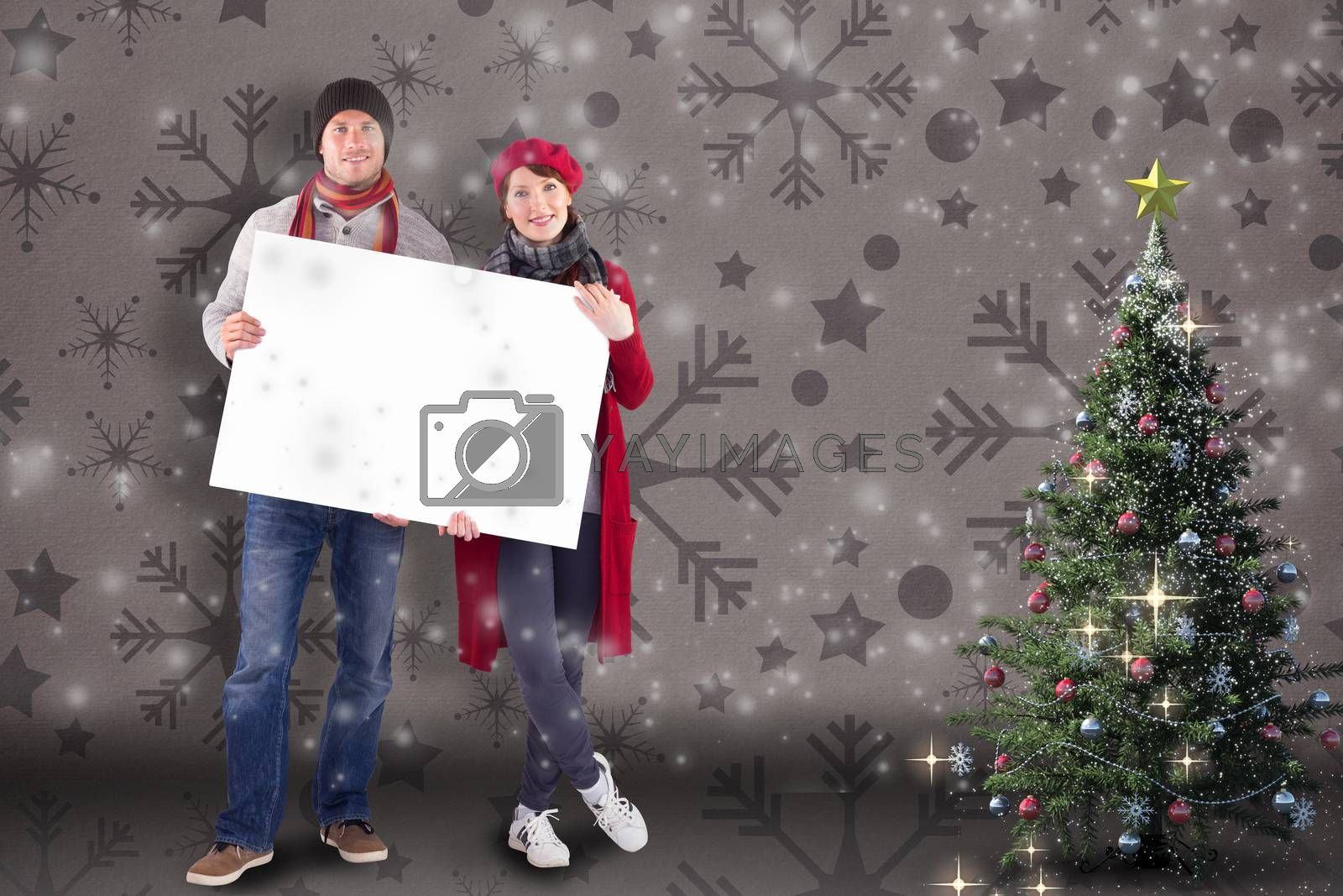 Couple holding a large sign against snowflake wallpaper pattern