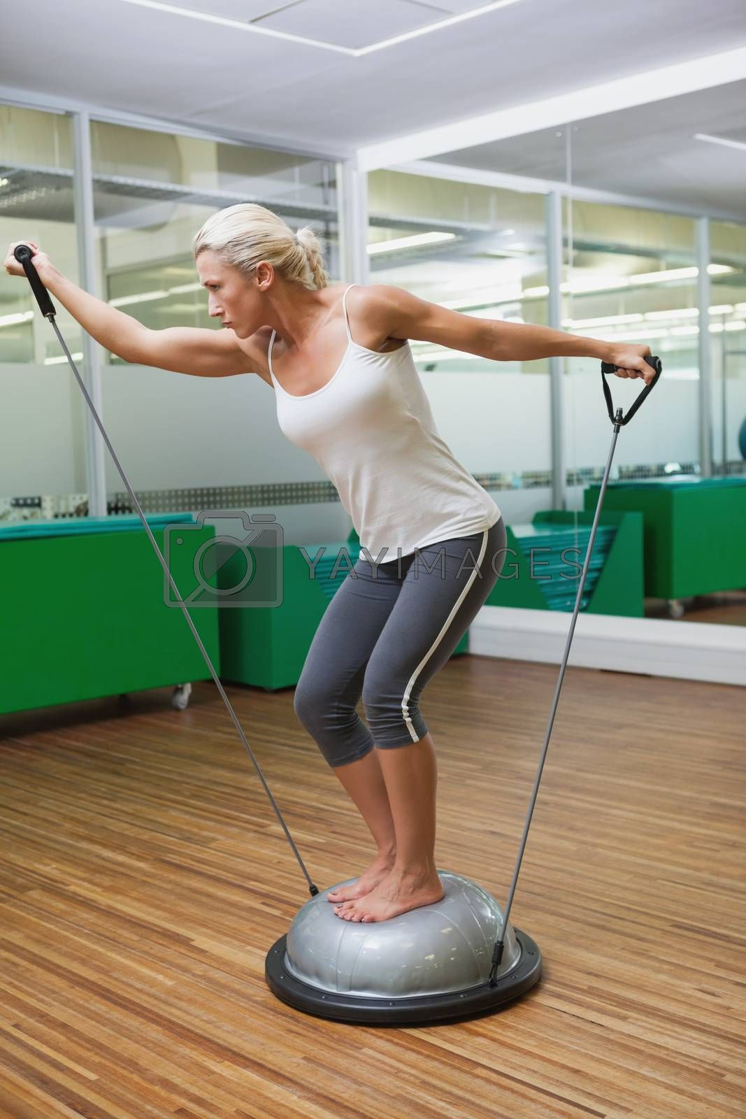 Full length side view of a young woman doing fitness exercise in fitness studio