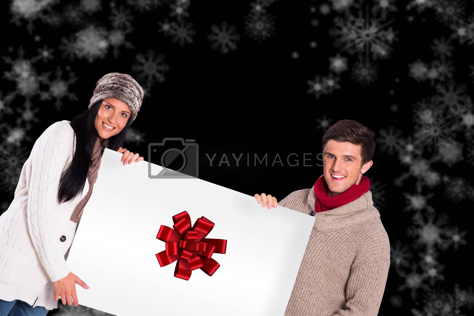 Young couple holding a poster against red christmas ribbon