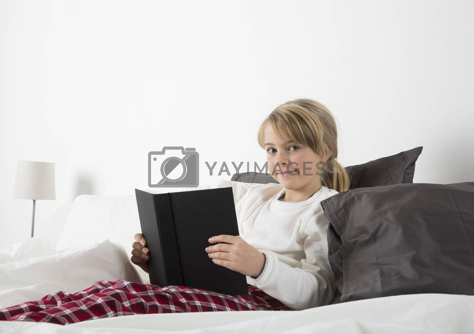 Young girl with a book in bed look in the camera
