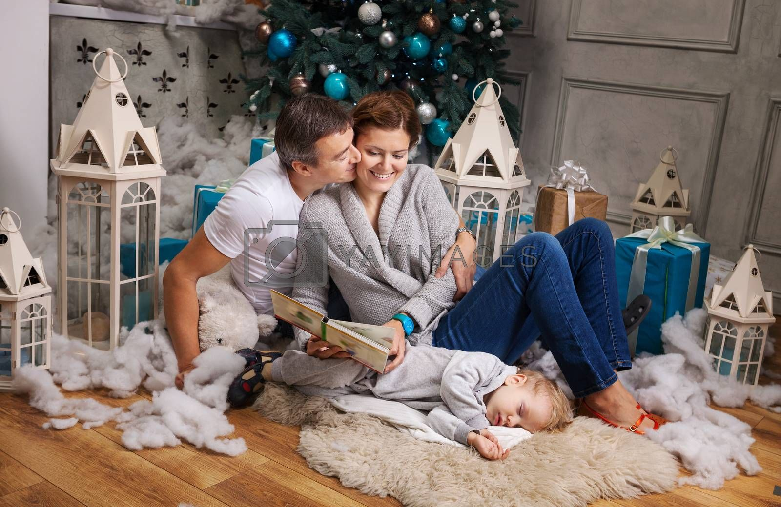 Cheerful couple reading book to toddler son beside Christmas tree, boy falling asleep