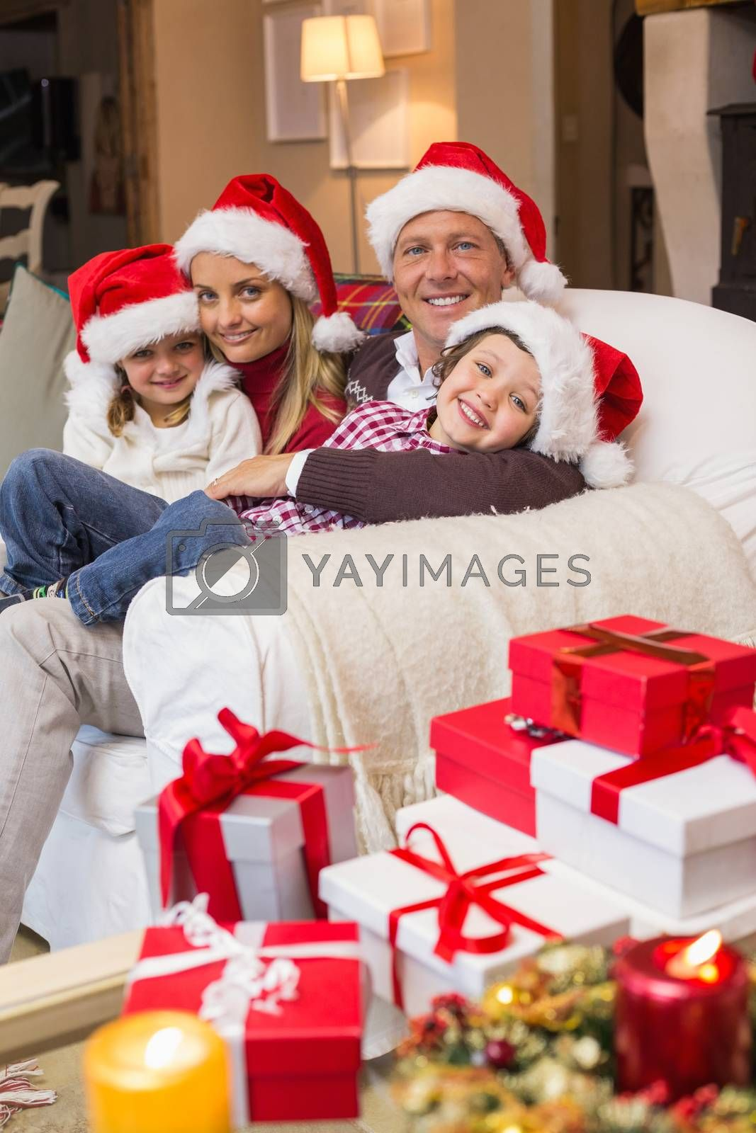 Festive family in santa hat hugging on couch at home in the living room