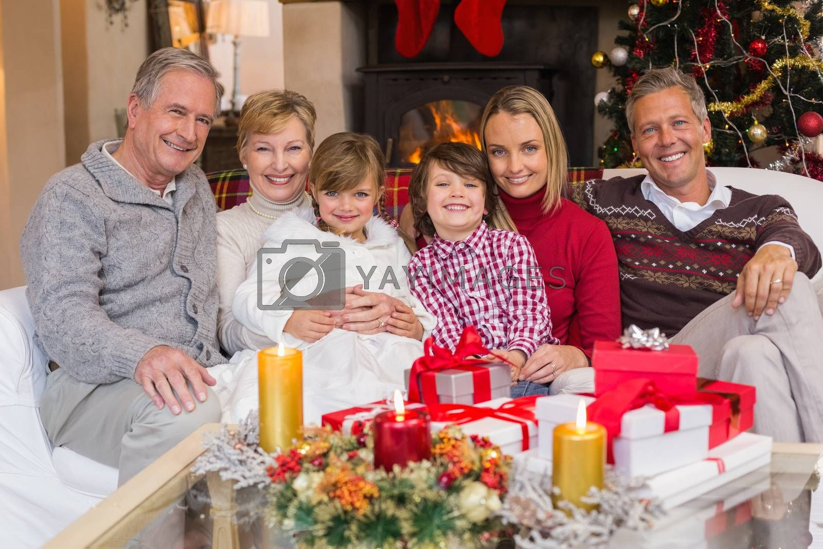 Multi generation family smiling at camera during christmas at home in the living room