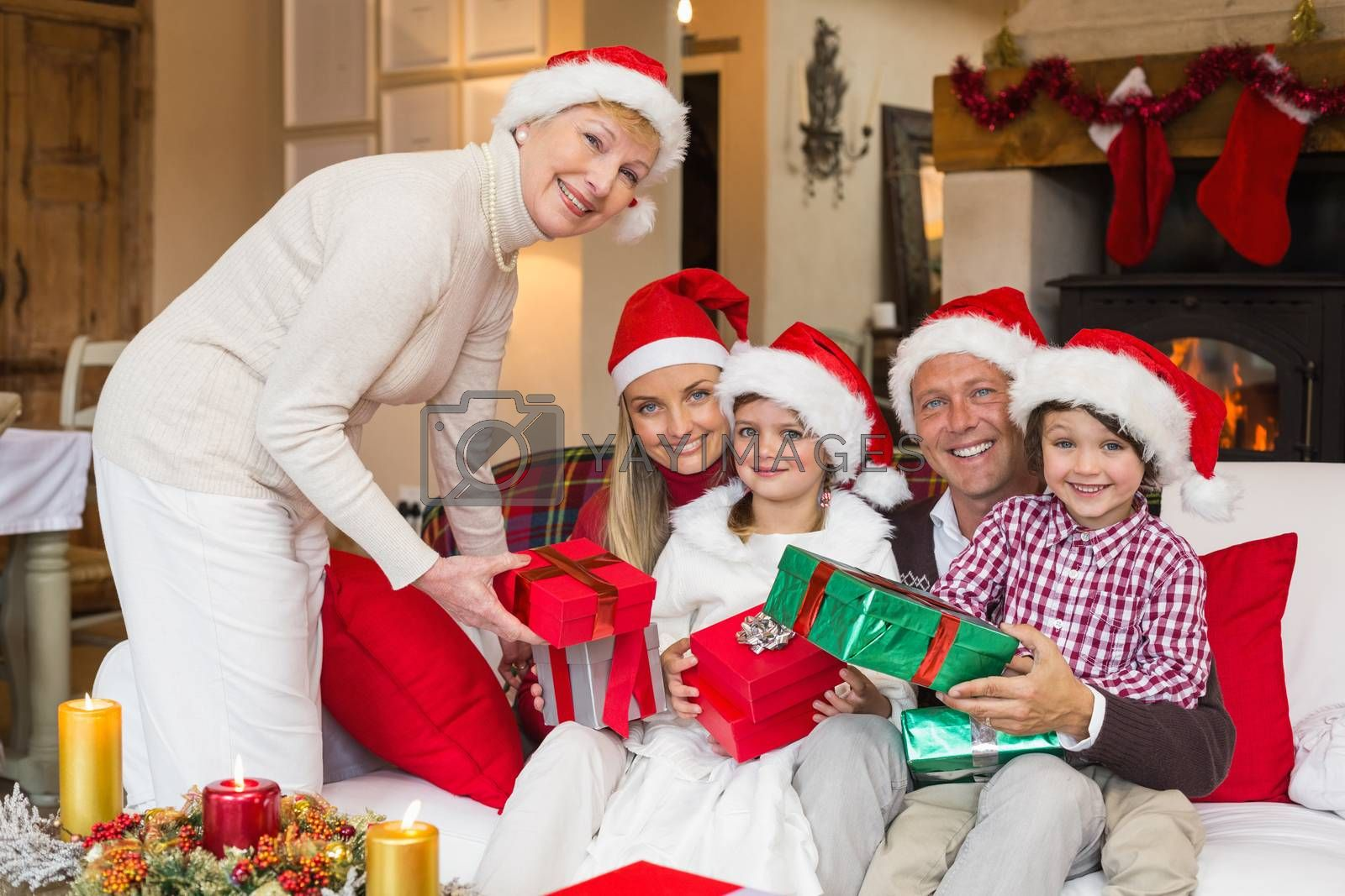 Smiling grandmother giving gift to her family at home in the living room