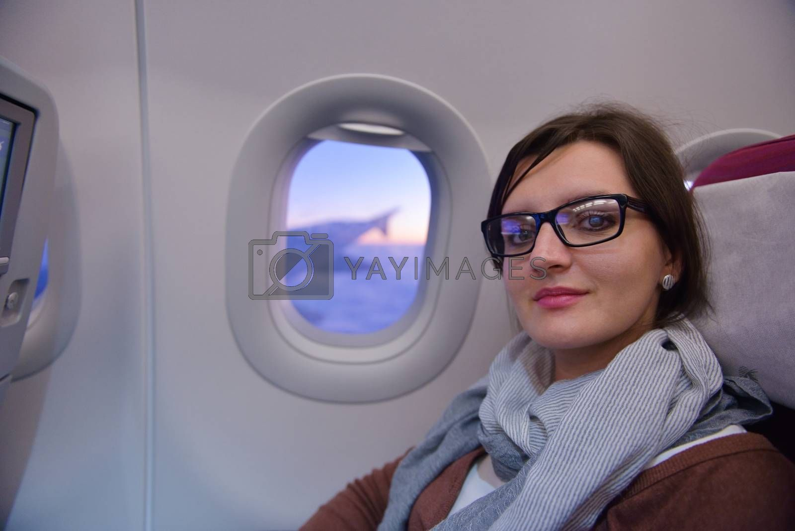 happy young  tourist  woman is sitting in the airplane looking windov and travel to summer vacation