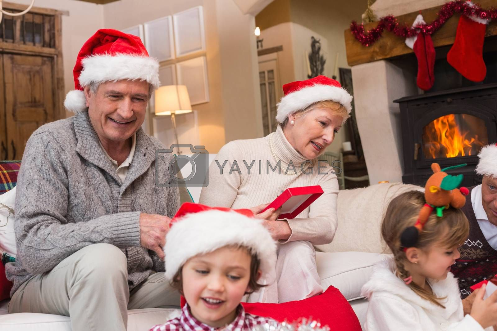 Happy family opening christmas gifts together at home in the living room