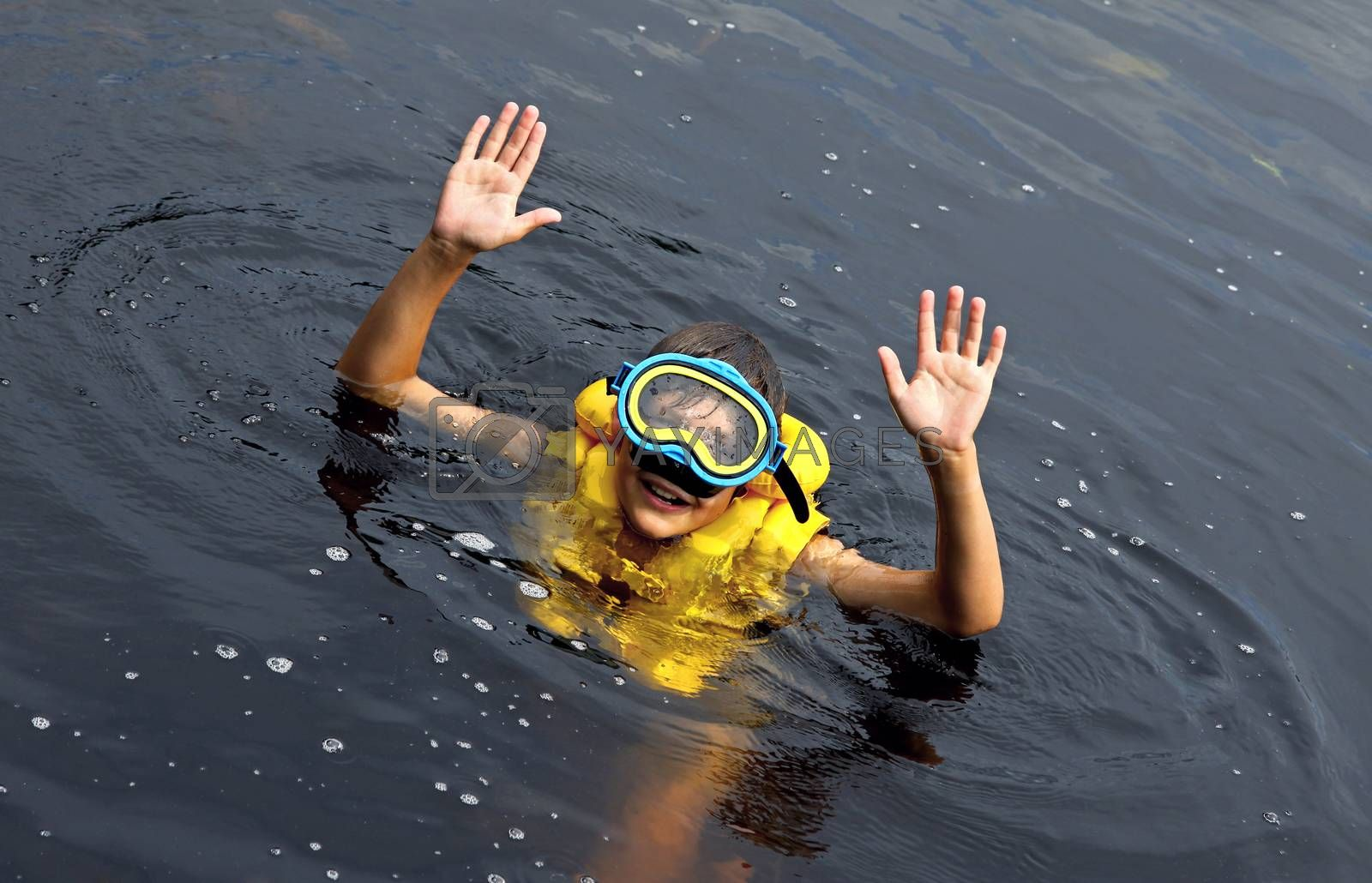 Young boy swimming in lake with swimming mask and swim vest