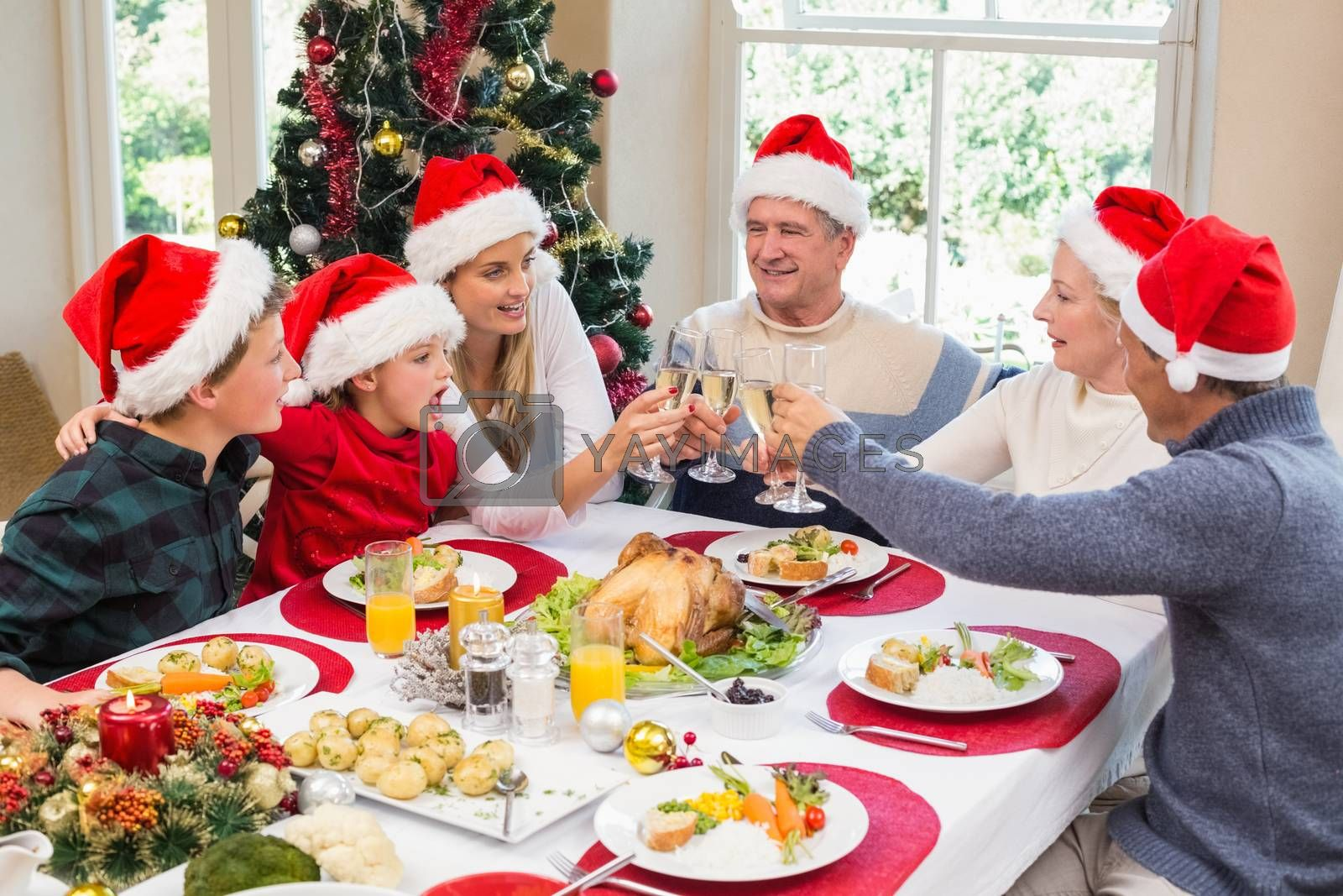 Multi generation family in santa hat toasting each other at home in the living room