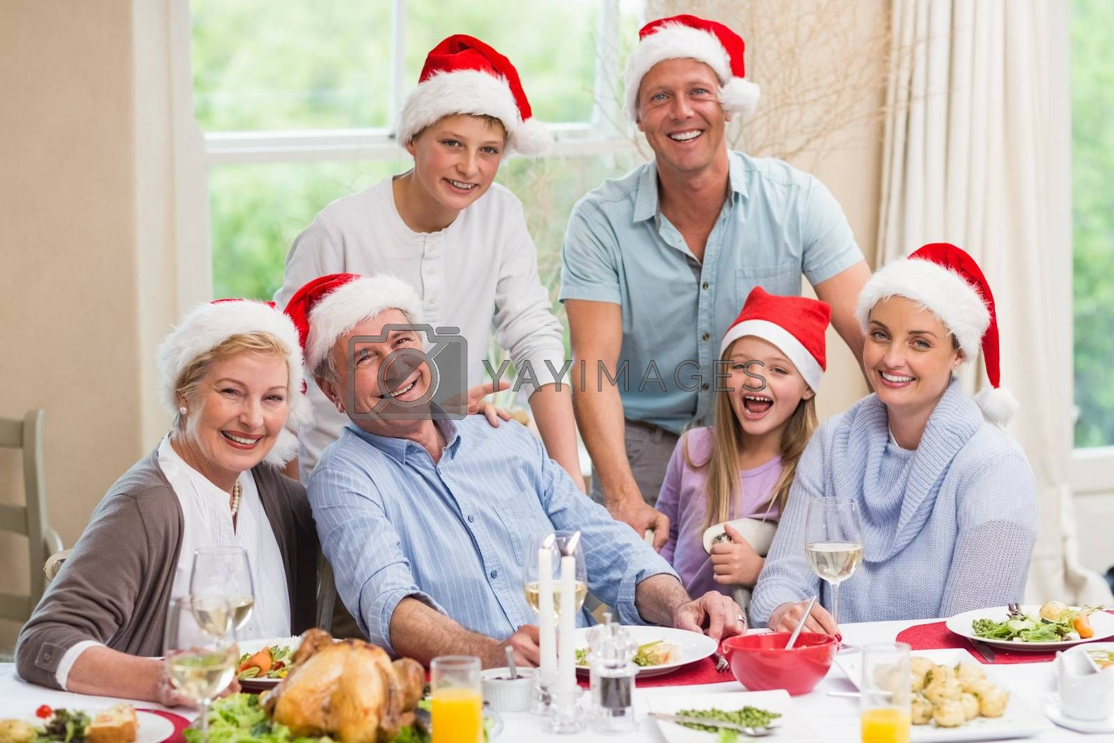 Happy family in santa hat looking at camera at home in the living room