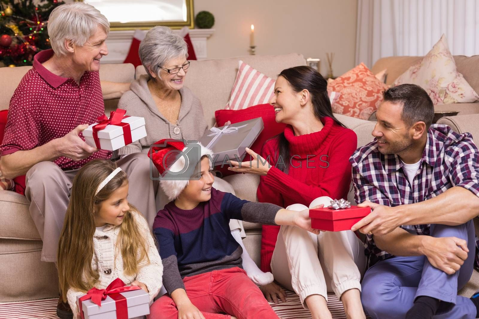 Multi generation family exchanging presents on sofa at home in the living room