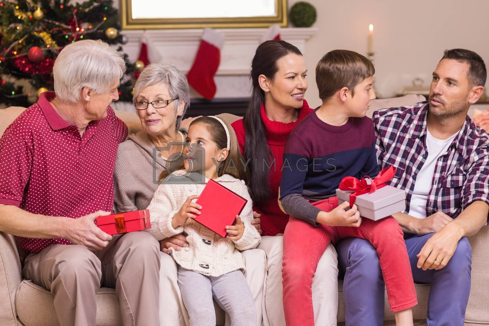 Multi generation family holding presents on sofa at home in the living room