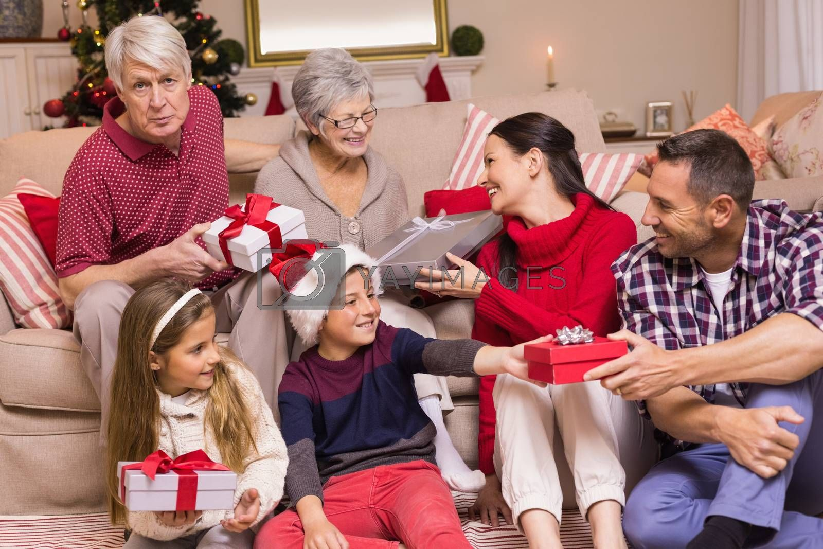 Multi generation family exchanging presents on couch at home in the living room
