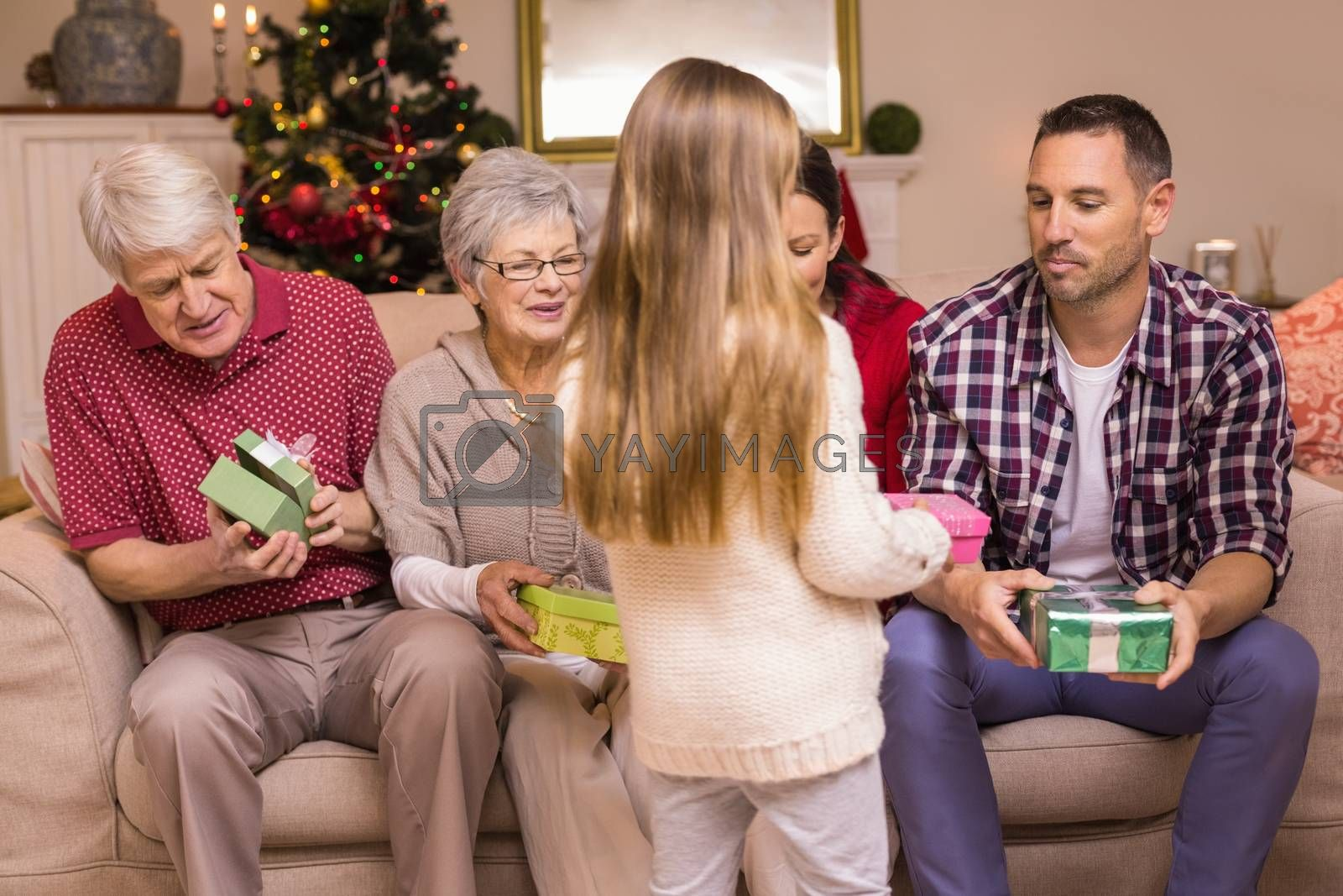 Cute little girl offering gift to her family at home in the living room