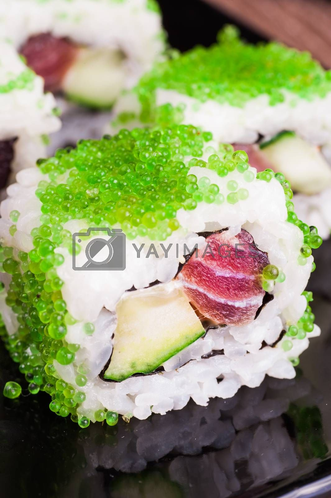 sushi roll set in green caviar on wooden background