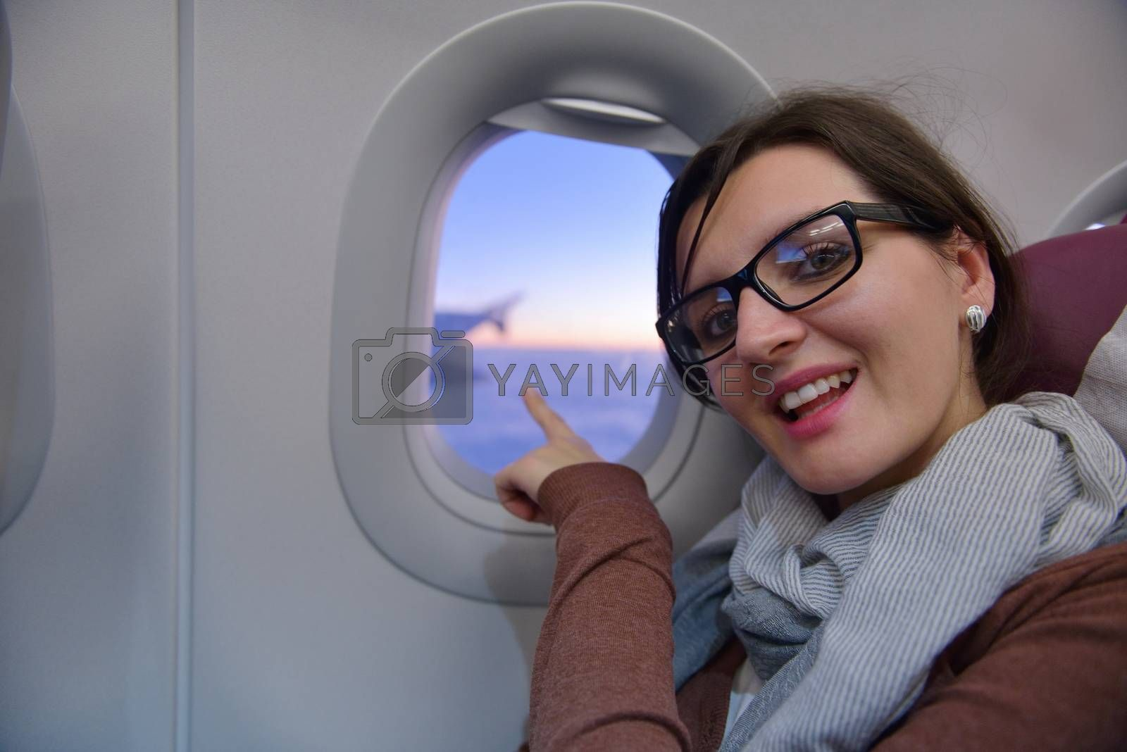 happy young  tourist  woman is sitting in the airplane looking window and travel to summer vacation