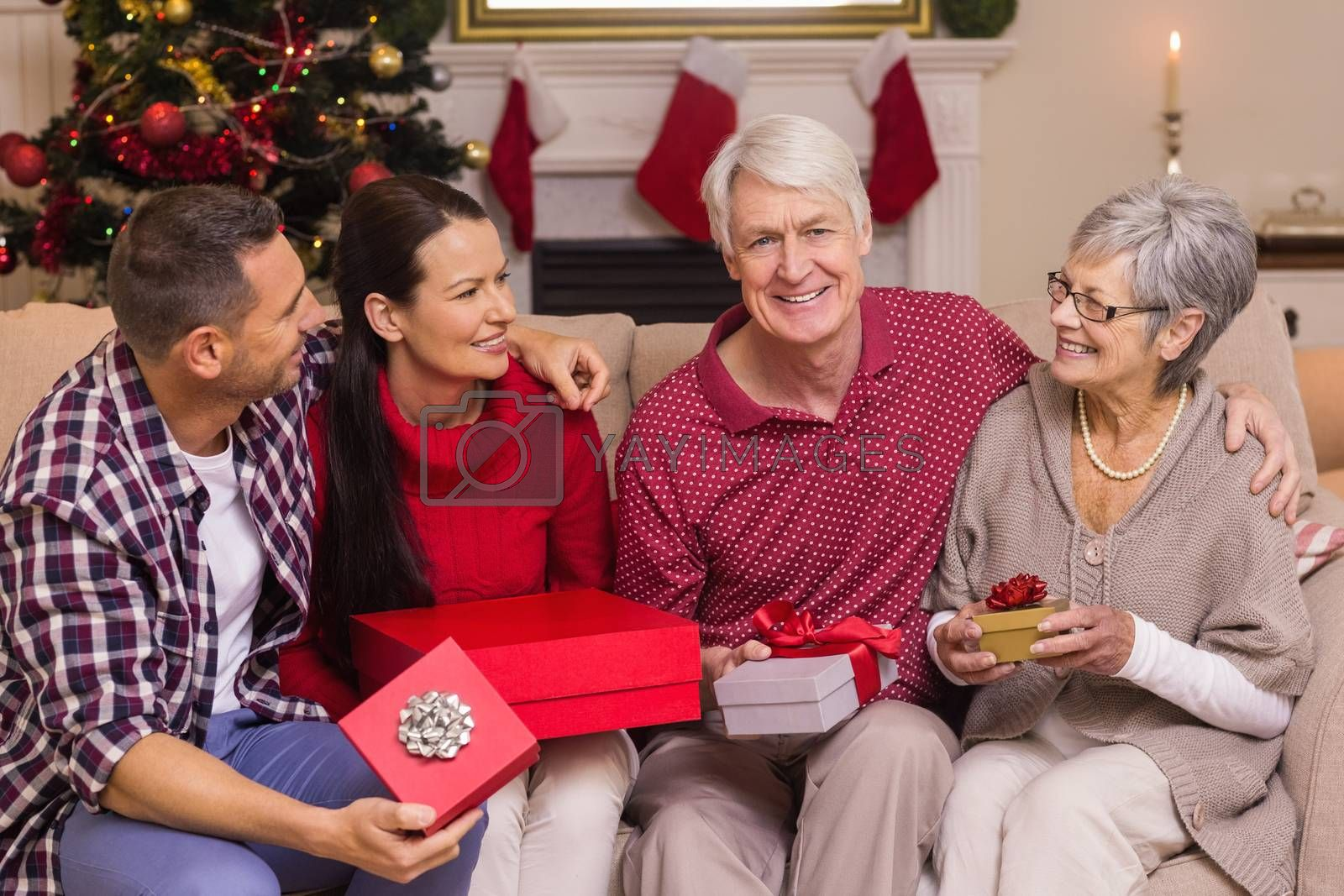 Smiling family holding gift on sofa at home in the living room