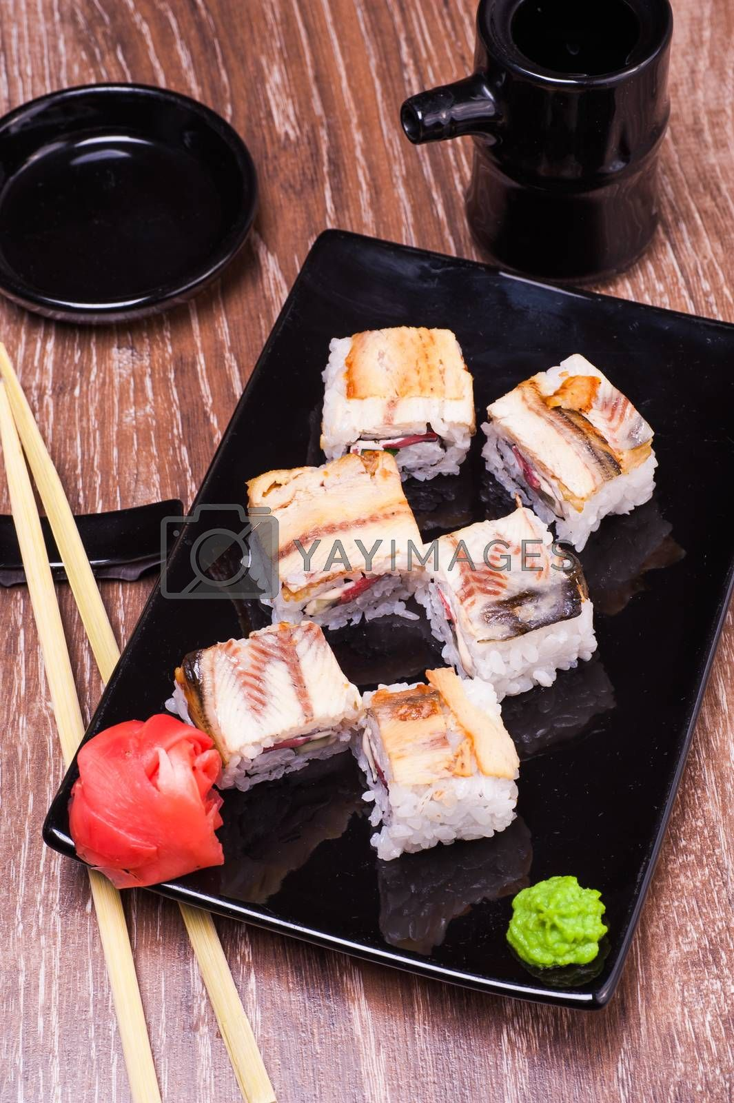 eel sushi roll  with ginger, soy sauce, towel and chopsticks n wooden background