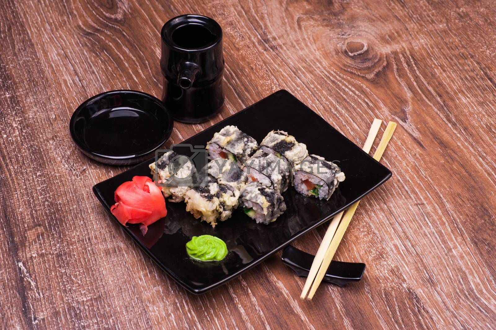 tempura sushi roll with ginger, soy sauce and chopsticks on wooden background