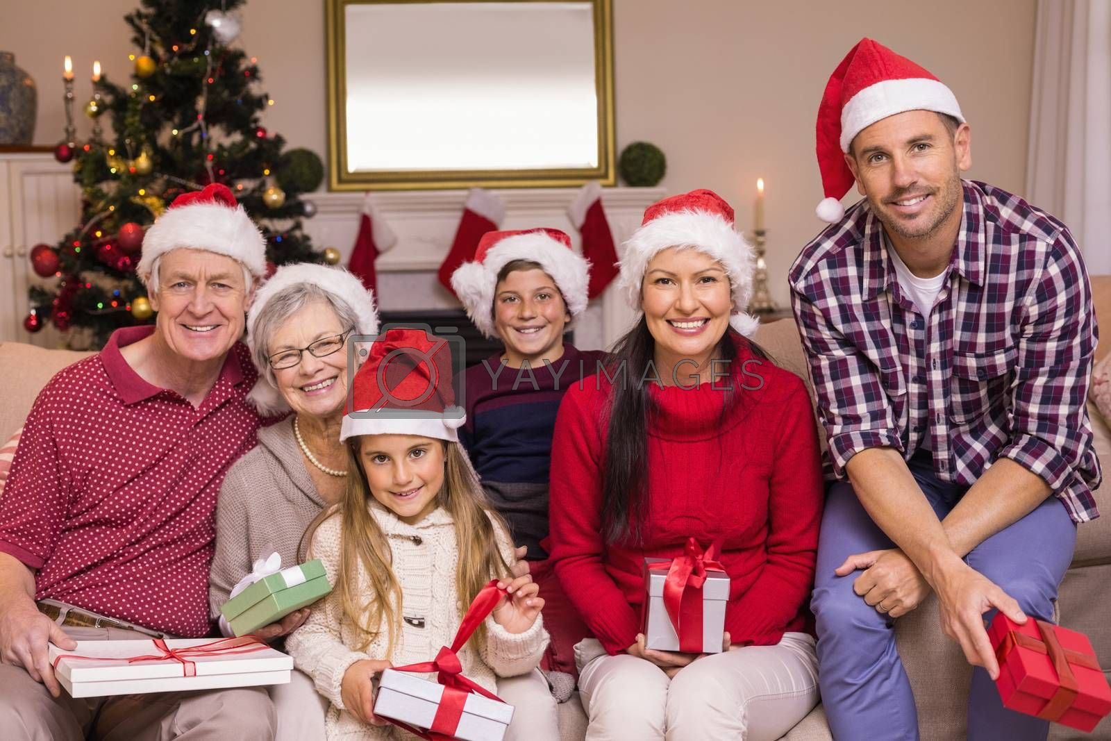 Multigeneration family wearing santa hats on the couch at home in the living room