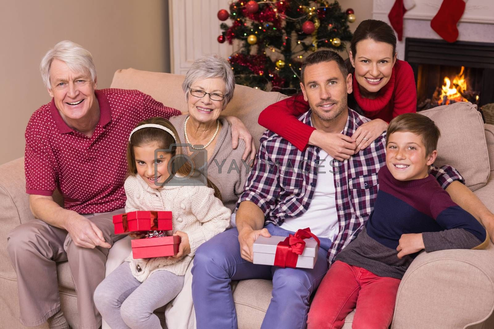 Multi generation family holding gifts on sofa at home in the living room