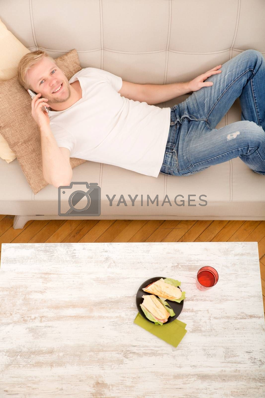 Young man with a Sandwich on the Sofa while talking on the phone.