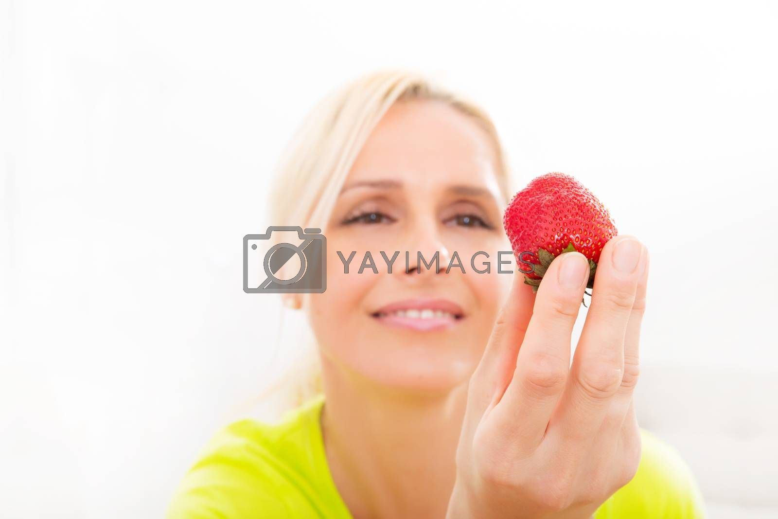 A beautiful mature woman eating strawberry at home.
