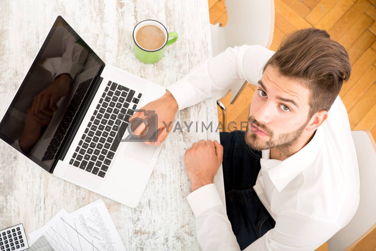 A young man working at home with a Laptop computer.