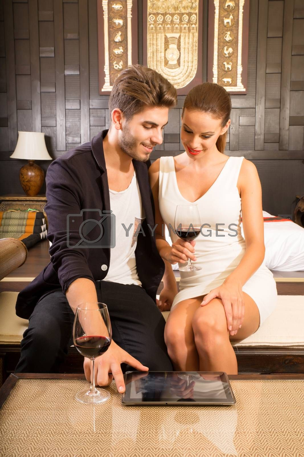 A young and happy couple enjoying a glass of wine in a asian style hotel room while using a tablet.