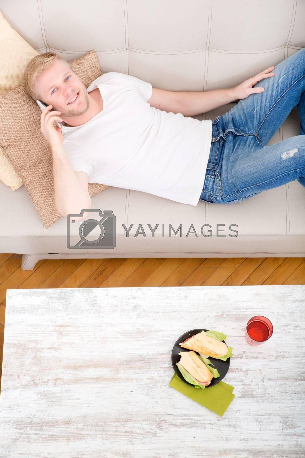 Young man with a Sandwich on the Sofa  by Spectral