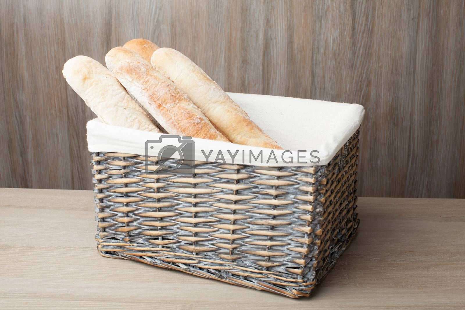Stack of traditional fresh-baked French bread loafs baguette served in woven basket on wooden background