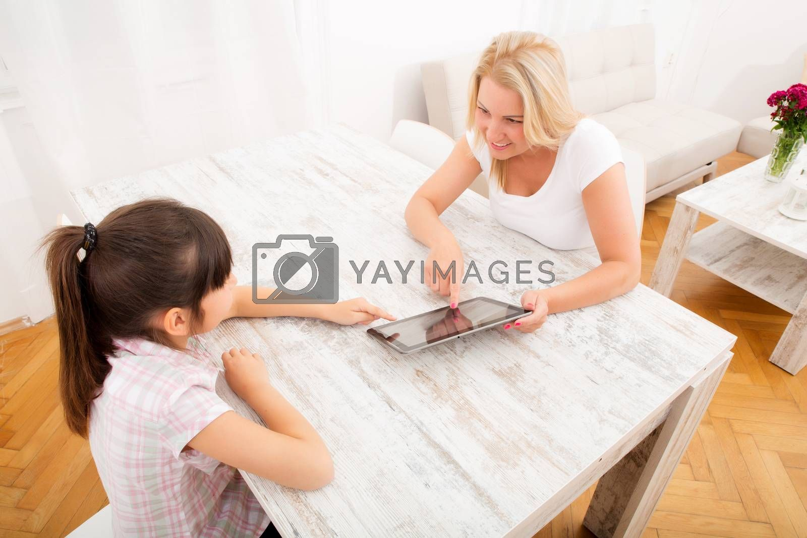 A mother with her daughter using a tablet PC at home.