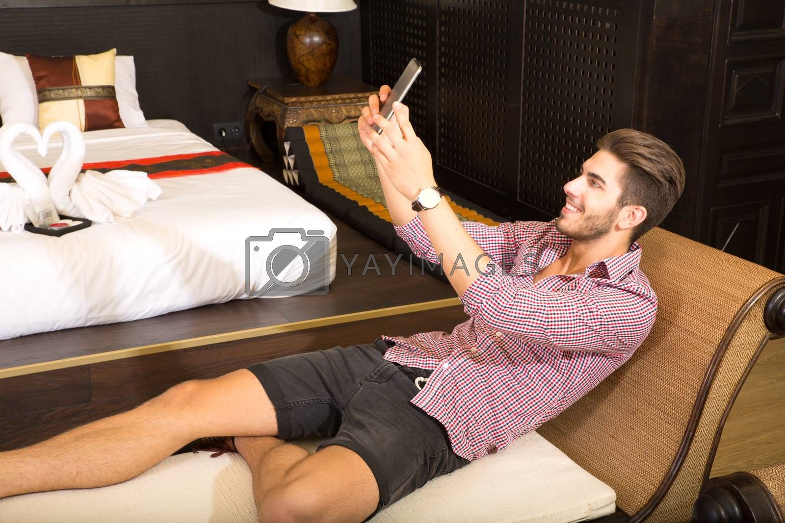 A handsome young man taking a selfie in a asian style hotel room.