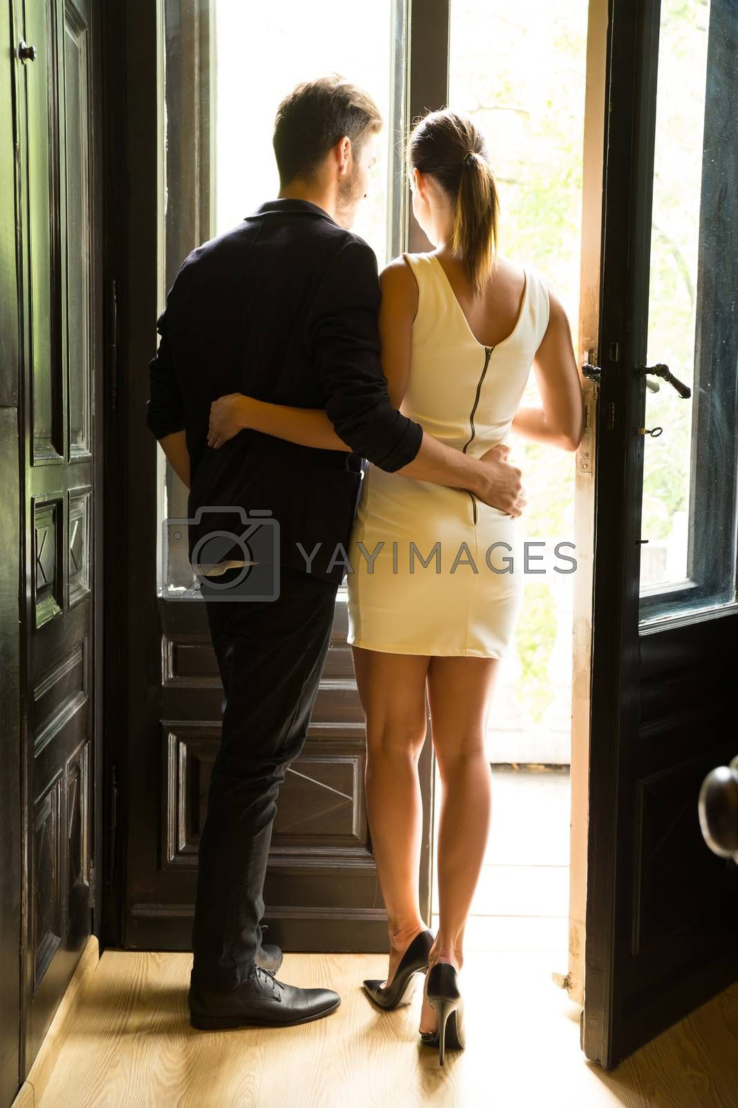 A young and beautiful couple standing at the window.