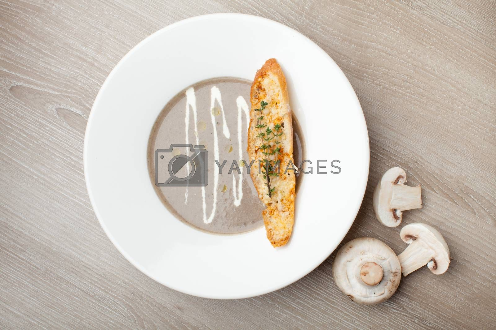 Vegetarian mushroom cream soup puree in white plate  with baked bread cheese slice