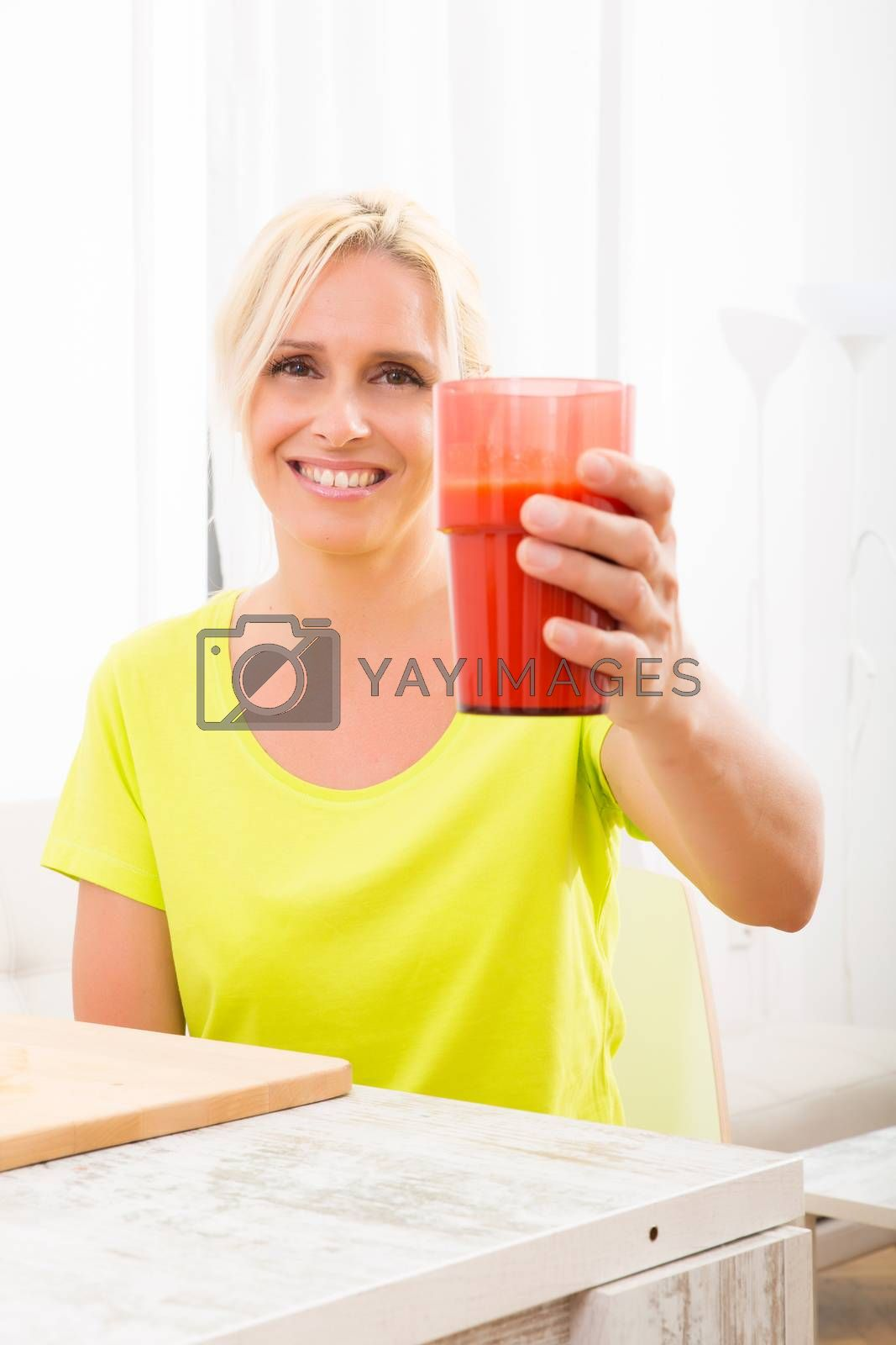 A beautiful mature woman enjoying a smoothie or juice with fruits in the kitchen.