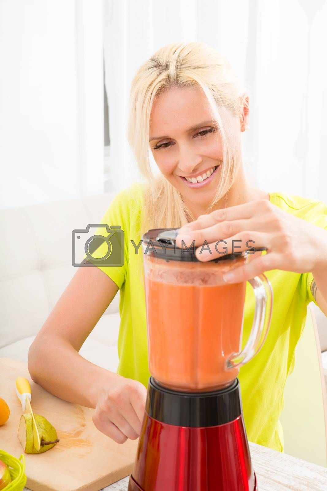 Mature woman blending a smoothie by Spectral