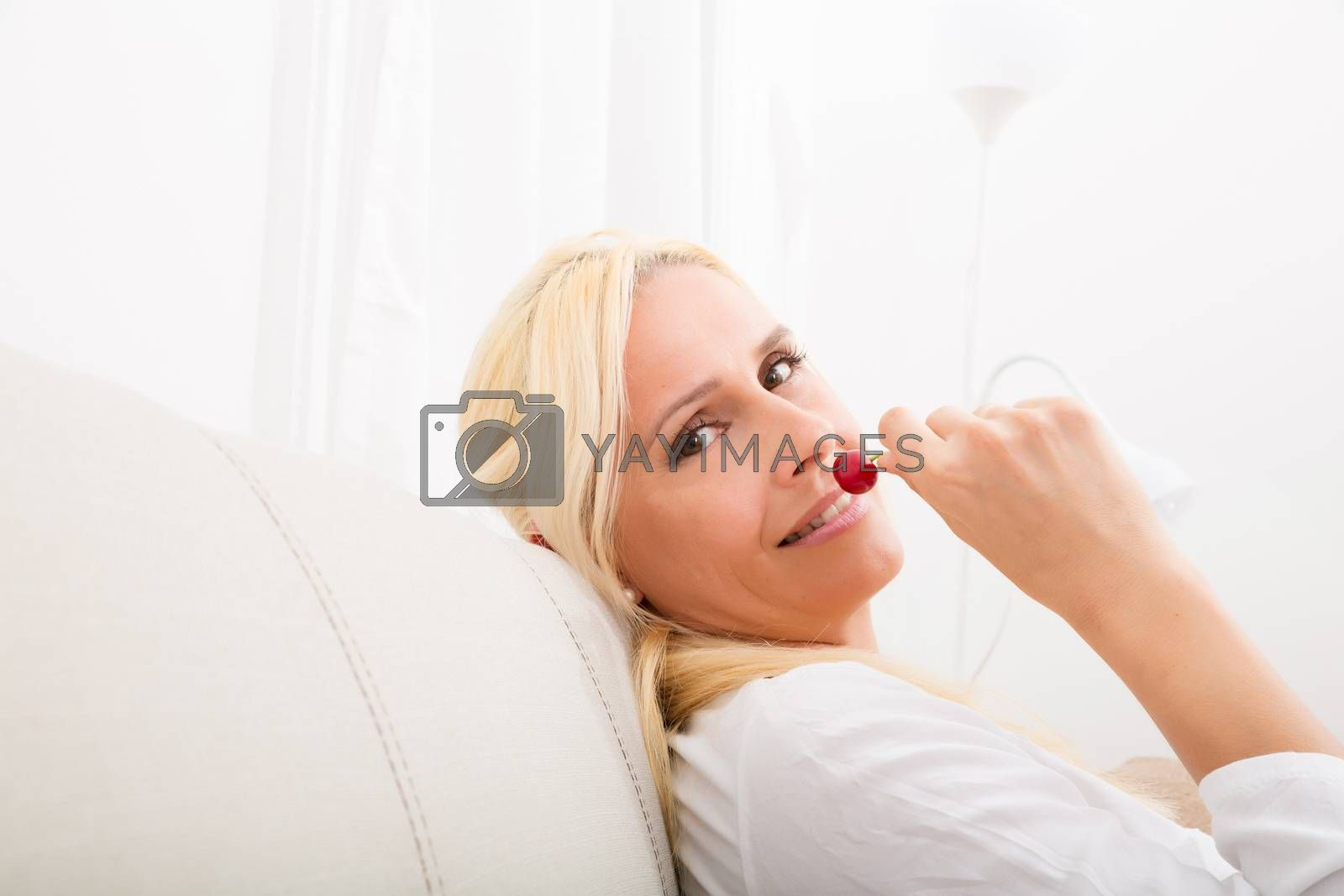 Woman eating cherry on the sofa by Spectral