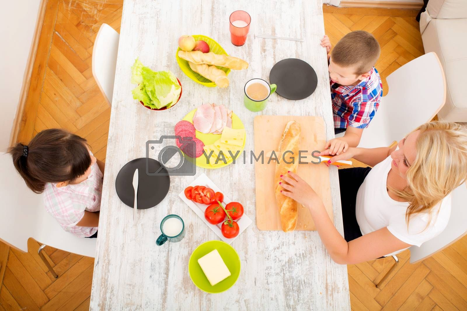 Happy family having breakfast at home by Spectral