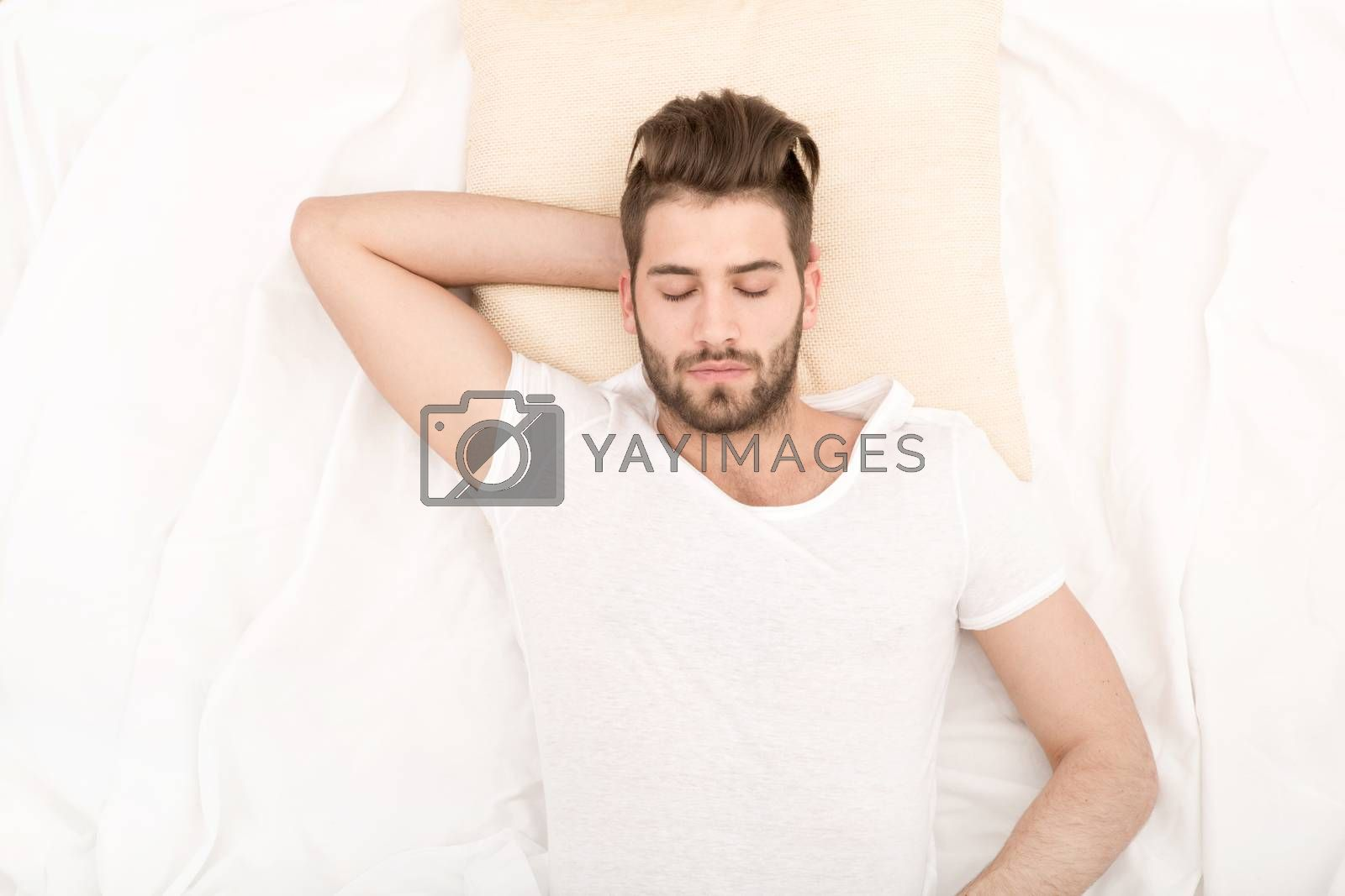 Portrait of a young man from above sleeping in a white bed.