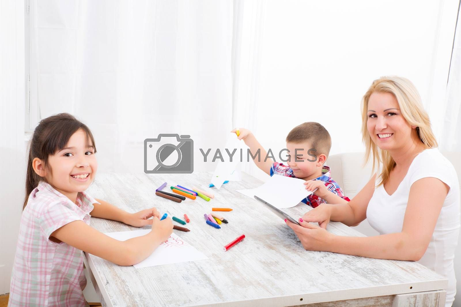 Mother and daughter and son at home at the table.