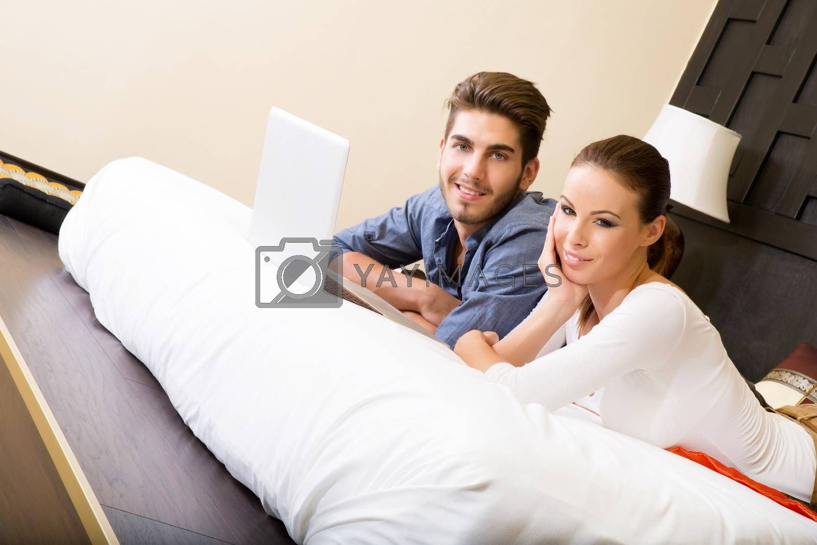 Young couple using a notebook in a asian hotel room while lying on the bed.