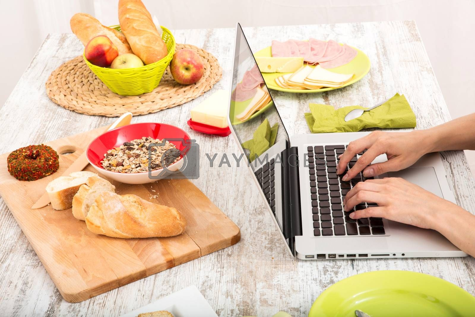 A young woman having breakfast while using a laptop computer.