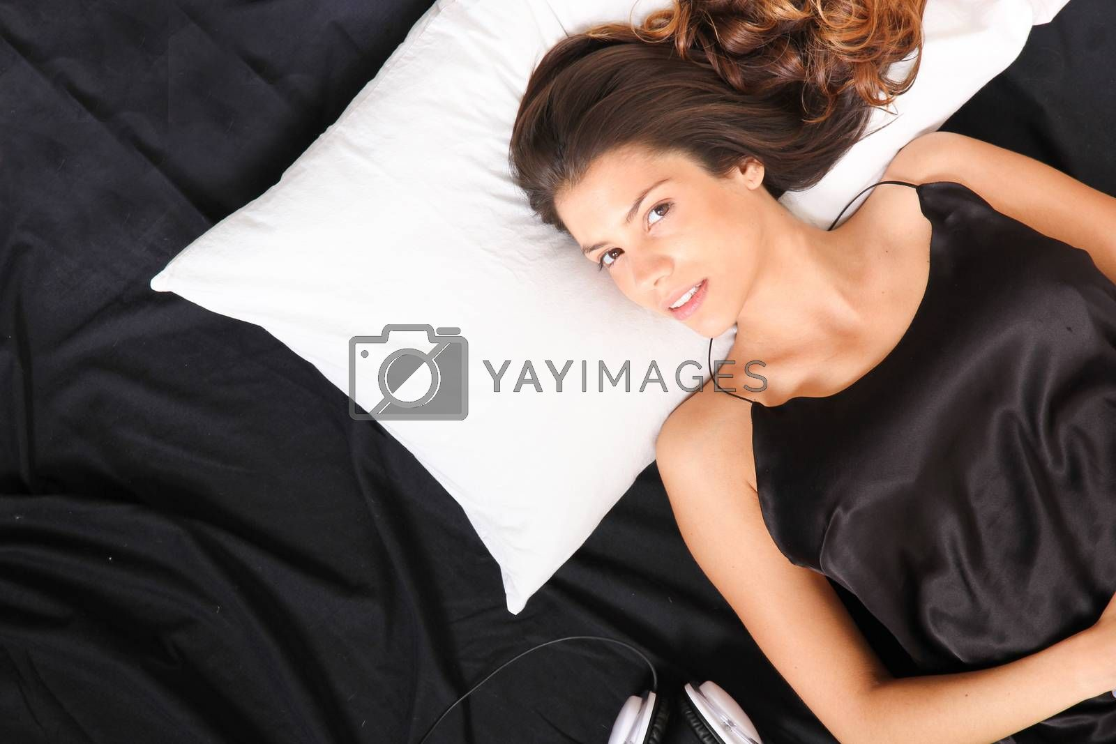 A young girl laying in bed, smiling with headsets
